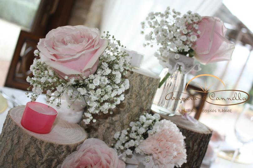Dettaglio centrotavola con tronchi e fiori e candele tenui.