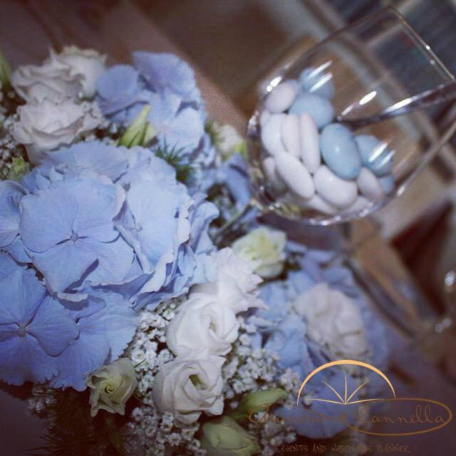 Centrotavola con fiori e confetti celesti.